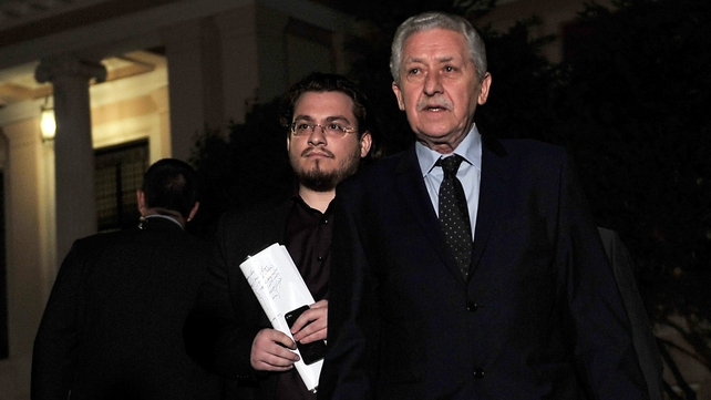 Fotis Kouvelis (R) leaves the Greek prime minister's office after a meeting of Greece's coalition leaders