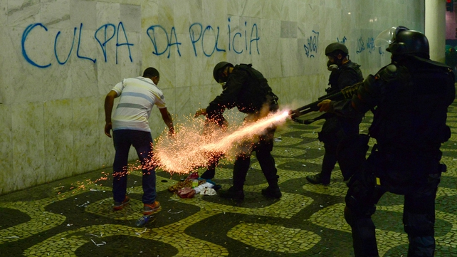 Anti-riot police officers fire tear gas cans during protests in Rio de Janeiro