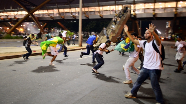 Demonstrators run away as anti-riot police officers charge them during clashes in Rio