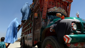 Afghan refugee women climb onto a truck at a United Nations High Commissioner for Refugees camp in Kabul
