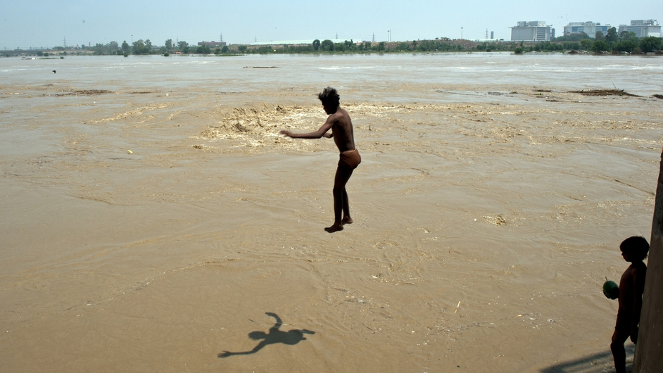 A young Indian boy dives into the rising waters of the Yamuna river in New Delhi