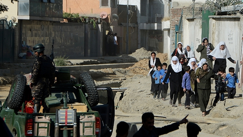 Afghan security forces keep watch as schoolgirls walk near the entrance gate of the presidential palace in the aftermath of attack