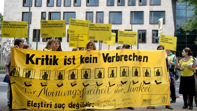 Protesters from Amnesty International gather outside Turkey's embassy in Berlin urging Turkey to respect the right to demonstrate