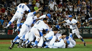 UCLA Bruins jump into a pile to celebrate after getting the final out against the Mississippi State Bulldogs during game two of the College World Series Finals