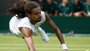 Dustin Brown of Germany dives to return a shot during his second-round match against Lleyton Hewitt at Wimbledon