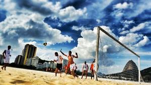 Men play football on Botafogo Beach in Rio de Janeiro