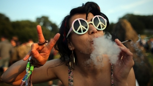 Rudina Hatipi smokes as she joins fellow revellers for the sunset at the stone circle at the Glastonbury Festival of Contemporary Performing Arts
