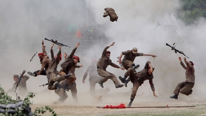 South Korean soldiers wear North Korea's military uniforms, acting as North Korean soldiers, as they take part in a re-enactment a battle of the Korean war in Chuncheon