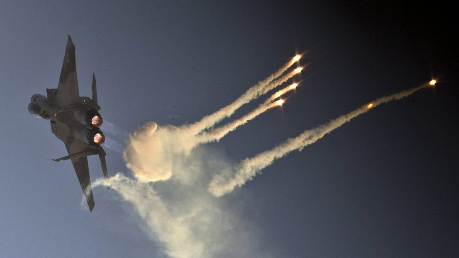 An Israeli fighter jet launches anti-missile flares during an air show at the Hatzerim base in the Negev desert