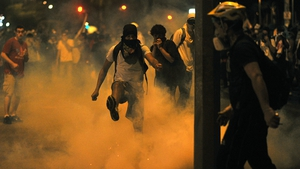 A demonstrator kicks a tear gas shell during clashes with the police outside the Mineirao stadium in Belo Horizonte, Brazil