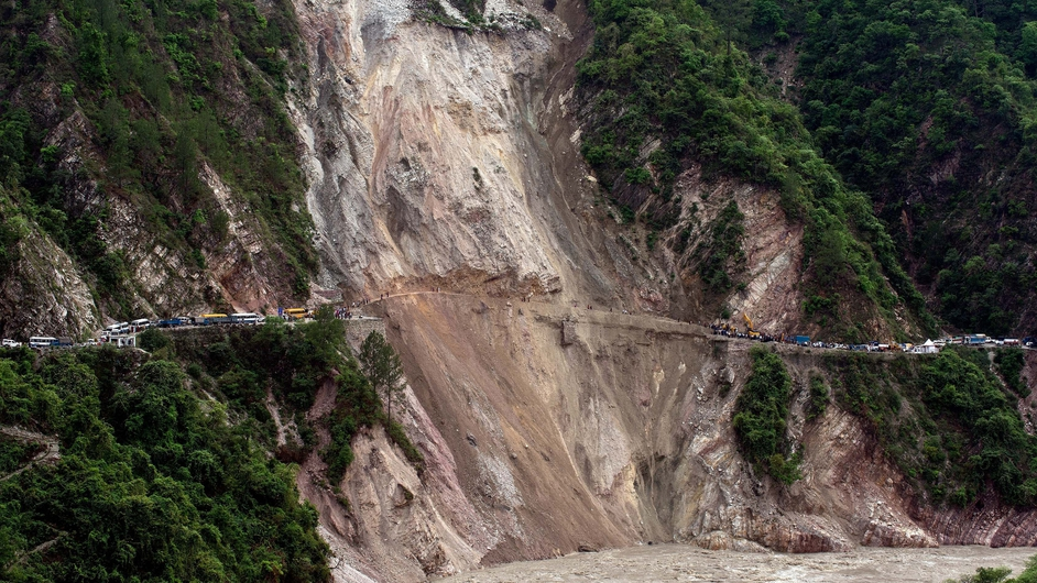 Vehicles wait on a road following a landslide due to heavy rain between Rudraprayag and Srinagar in India