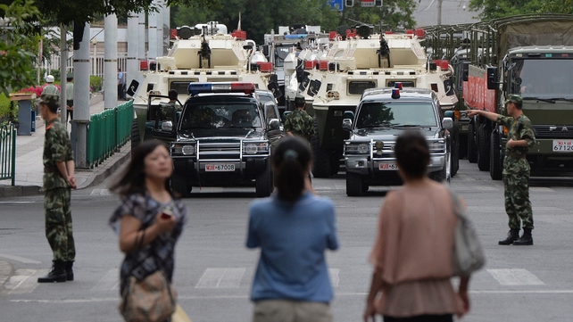 "People watch as paramilitary police prepare to ride in armoured vehicles during a ""show of force"" ceremony in Urumqi, following after a series of attacks in Xinjiang Province"