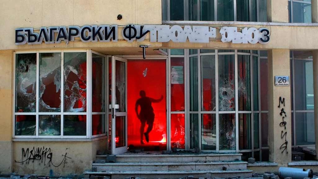 A CSKA Sofia football club supporter runs into the Bulgarian Football Union building in Sofia