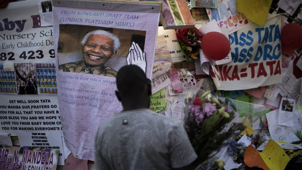 A man holds flowers in front of notes left by well wishers to former president Nelson Mandela