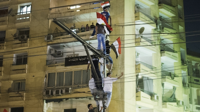 Protesters waving national flags climb on a railway pole outside the Presidential Palace