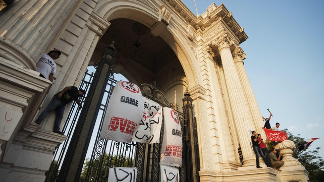 Protesters climb on the gate of the Qoubba Presidential Palace to hang signs calling for Mr Mursi to step down