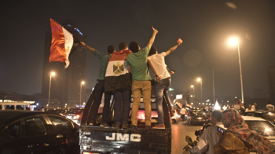 Egyptian youths on a police vehicle celebrate in Cairo