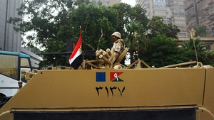 Egyptian military stands guard at a roadblock in the district of Giza