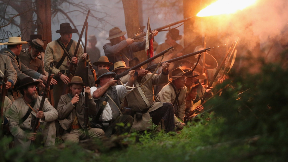 Confederate Civil War volunteers launch an evening attack during a three-day Battle of Gettysburg re-enactment