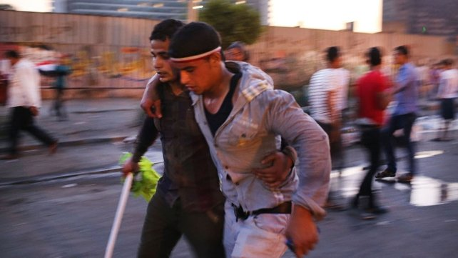 An anti-Mursi protester is attended to after allegedly being injured by Muslim Brotherhood supporters in Tahrir Square
