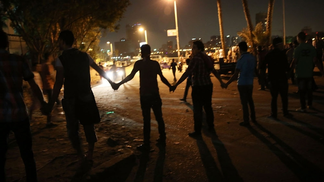 A group tries to keep people away from the 6 of October Bridge following clashes between anti-Mursi crowds and Muslim Brotherhood members