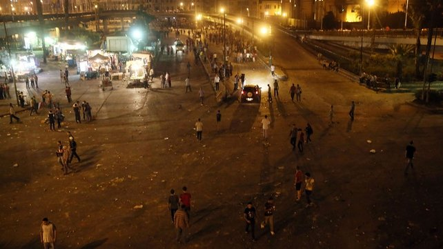 People walk in the street under the 6 of October Bridge following clashes