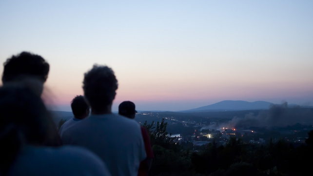 Residents view the disaster from a hill overlooking the town