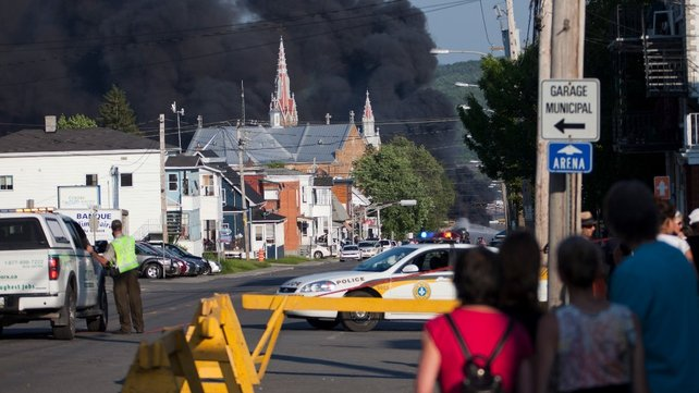 People watch black smoke billowing in the sky over the town centre
