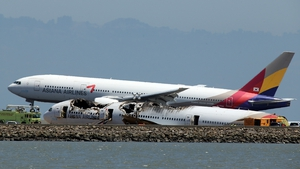 An Asiana Airlines flight lands beside the wreckage of Asiana 214 at San Francisco International Airport