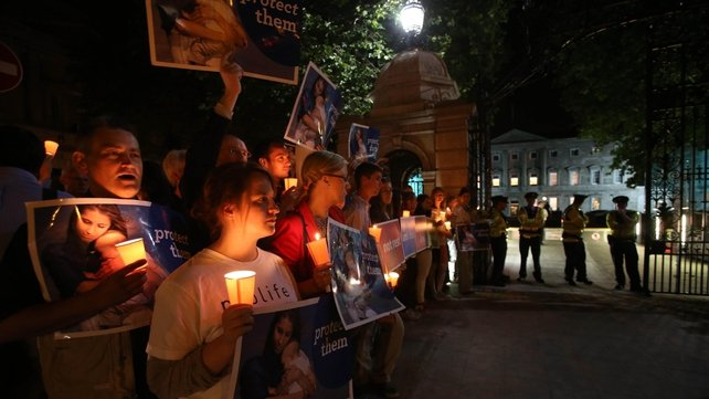 Anti-abortion protesters hold a vigil outside Leinster House after the bill was passed