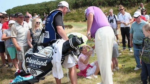 Shane Lowry gives a signed glove to a spectator he hit with his tee shot on the 8th hole