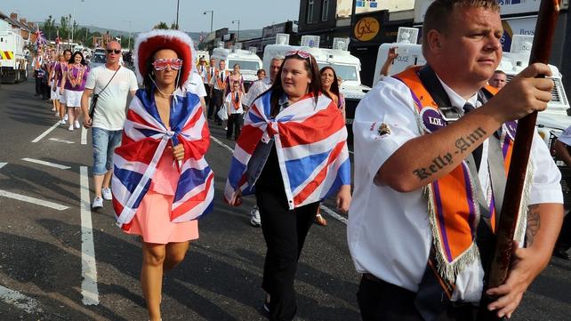 An Orange feeder parade walks past the Ardoyne shops in Belfast