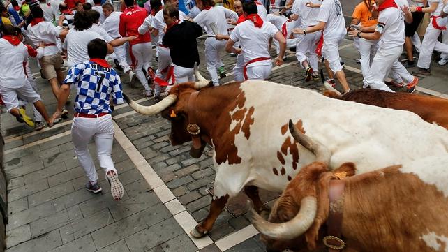 Revellers and bulls run through Pamplona's narrow streets