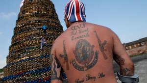 A man stands guard over a bonfire near the loyalist Shankill road in Belfast