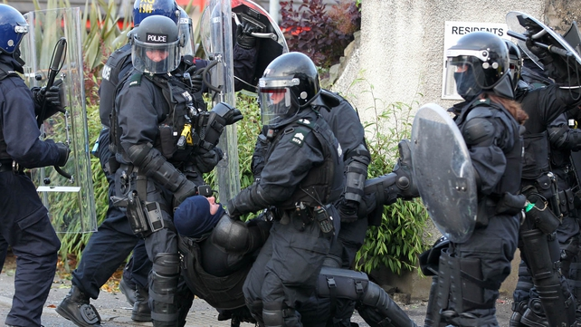An injured policeman is carried away during clashes with protesters in Ardoyne