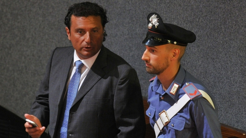 Francesco Schettino speaks to a policeman as he takes his place for his trial in Grosseto