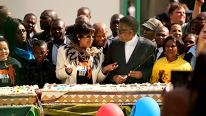 Winnie Madikizela- Mandela, ex-wife of Nelson Mandela, stands with a giant birthday cake outside the Mediclinic Heart Hospital