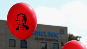 Balloons bearing the former president's image float outside the Mediclinic Heart Hospital