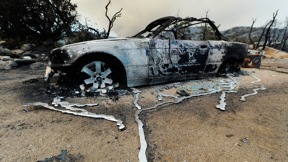 Liquefied metal drips from a burned-out car after mountain fires in Idyllwild, California