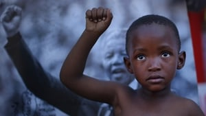 A young boy poses in front of an image of Nelson Mandela during the former South African president's 95th birthday celebrations