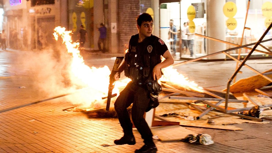 A policeman clashes with protesters during riots in Istanbul, Turkey