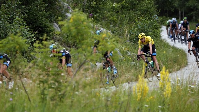 The yellow jersey of Chris Froome seen from a distance