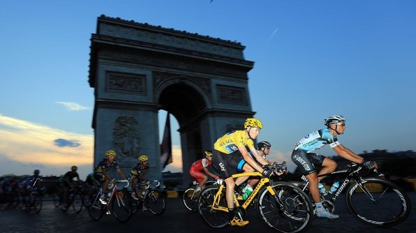 Chris Froome in the famous yellow jersey rounds the Arc d'Triomphe on his way to winning in Paris
