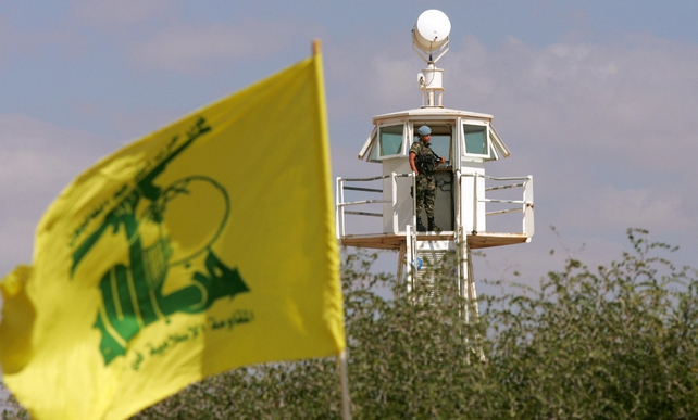 A Hezbollah flag flies as a member of the UN Interim Force in Lebanon stands in a lookout tower