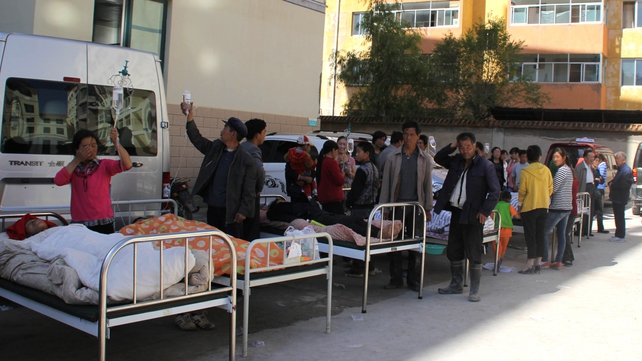 Injured people are treated on beds outside a hospital in Minxian County