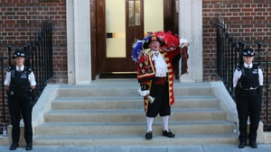 A town crier stands outside the hospital to announce the birth of a baby boy