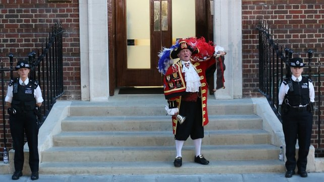 A town crier announces the birth of the royal baby on the steps of the Lindo Wing