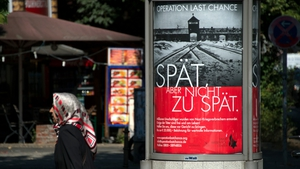 The poster features the infamous gates of Auschwitz along with the slogan 'Late, but not too late'