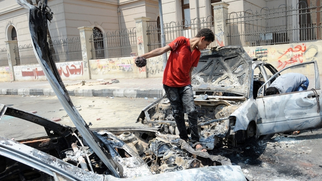 An Egyptian youth inspects a burnt car near Cairo University