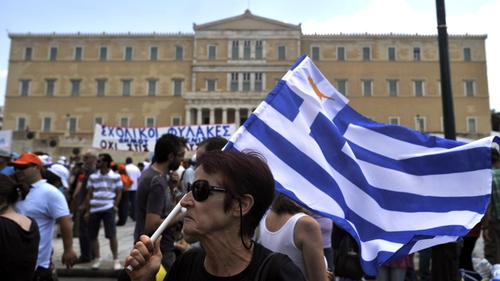 A woman holds a Greek flag in front of parliament buildings in Athens during a recent general strike